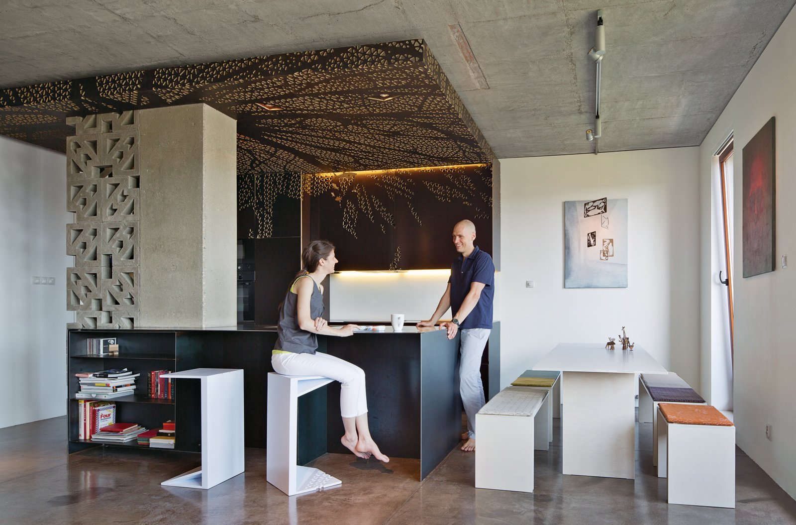 Nix and Novak-Zemplinski, founders of the design firm BioLINIA, in their 1,000-square-foot apartment's open-plan kitchen, dining, and living space. They had the decorative cabinets and ceiling panels CNC-milled by a Polish subsidiary of the Finnish company Koskisen. Photo by Andreas Meichsner.