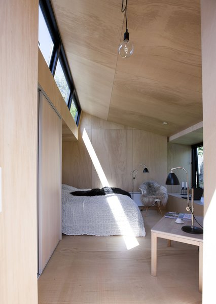 In Præstø, on the Danish island of Zealand, a guesthouse infuses the regional vernacular with Japanese influence. The interior is small, but comfortable. It fits a double bed, coffee table, and chair. The bed is recessed into the wall so as not to waste any space. Natural light floods the interior from a clerestory.