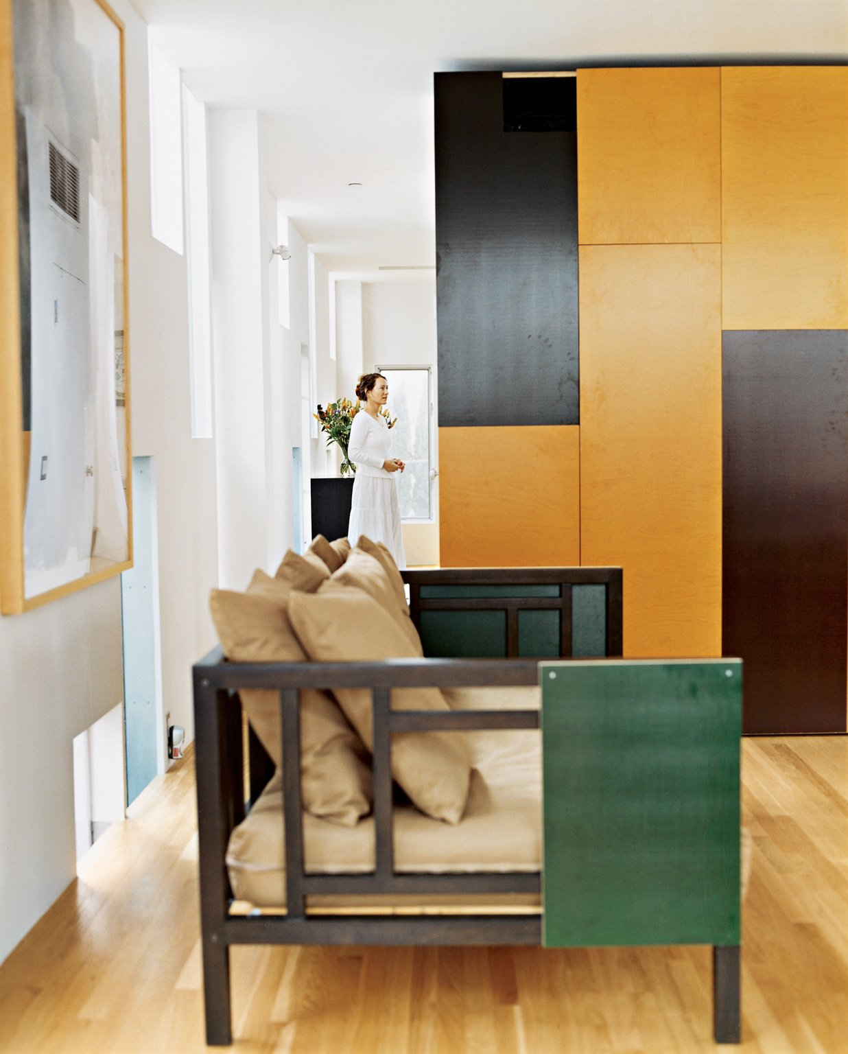 Operable panels of the built-in cabinetry, in chocolate and caramel colors, offer cues to the color palette of more mobile furnishings. Using the same panel material, the architect customized a West Elm couch for the living room.  Photo 4 of 8 in 8 Modern Paneled Rooms from Kaleidoscopic Cabinet