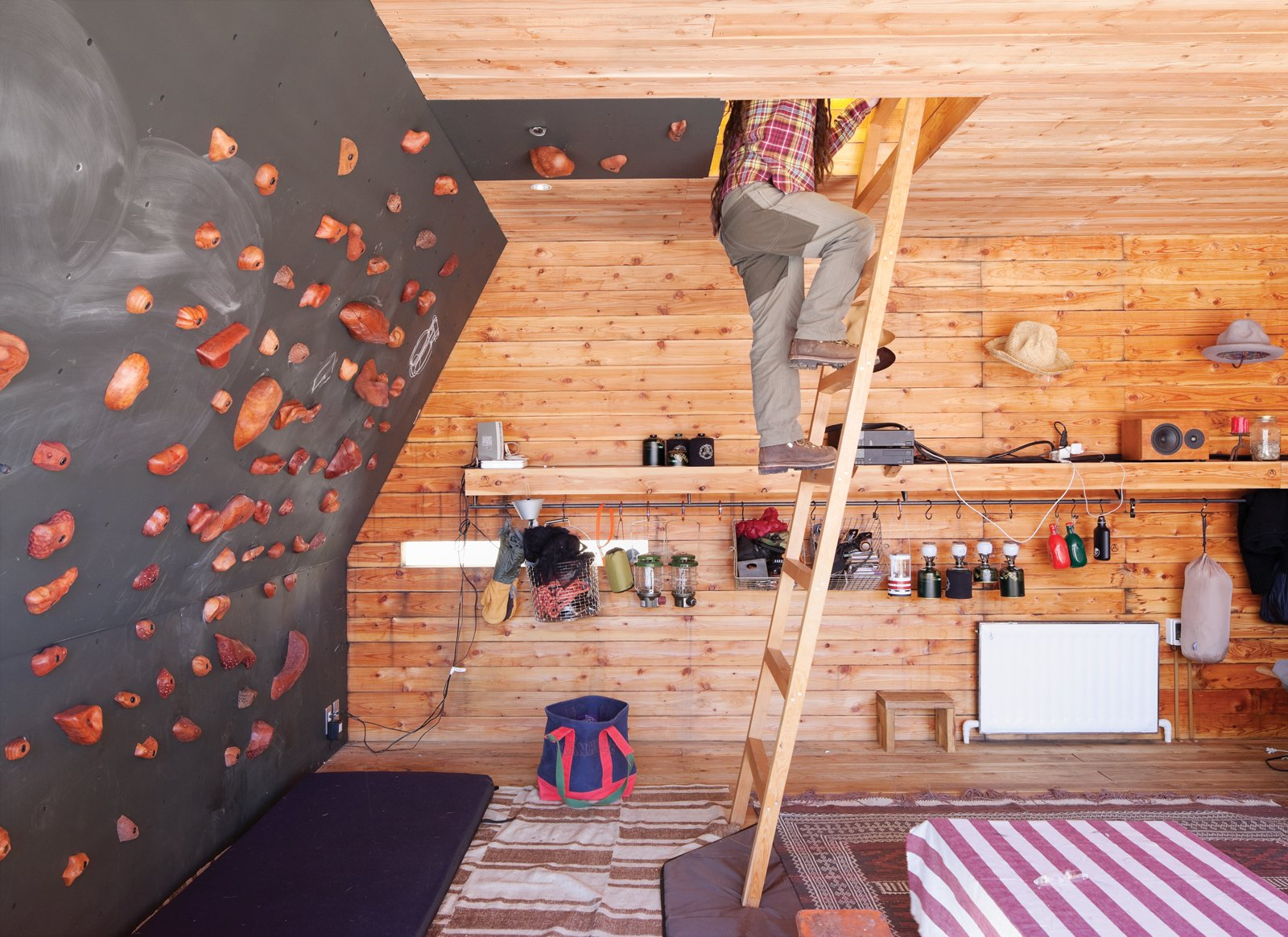 The rooftop tent can be accessed from the interior via a wooden ladder or—for the more athletic—via a series of wall-mounted climbing holds, made by Vock and carved from persimmon-tinted hardwood. Tagged: Living Room and Shelves.  Woodgrain by Jenny Xie from A Platform for Living