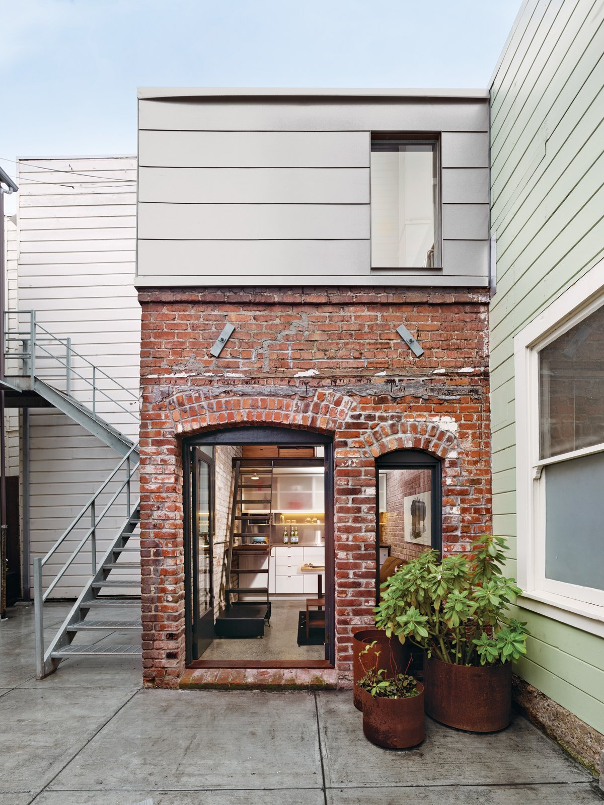 A COMPACT THREE-STORY BRICK LOFT IN SAN FRANCISCO  Making the most of vertical space unleashes the potential of a petite San Francisco project.  Photo by Cesar Rubio. Tagged: Concrete Patio, Porch, Deck, Small Patio, Porch, Deck, Back Yard, Exterior, House, and Brick Siding Material.  Brick Houses from Around the World  by Matthew Keeshin from A Compact Three-Story Brick Loft in San Francisco