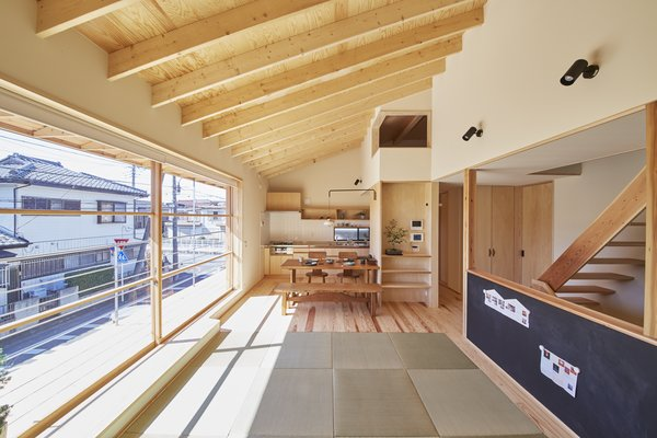 Modern home with living room, bench, wall lighting, and light hardwood floor. The 13-foot-wide sliding window provides abundant natural light year-round. The staircase was placed at the building's center to maximize openness and make space for the carport below. The blackboard is for the couple's young son, Takuma, to play with and practice writing. Photo 2 of Yanagisaki House