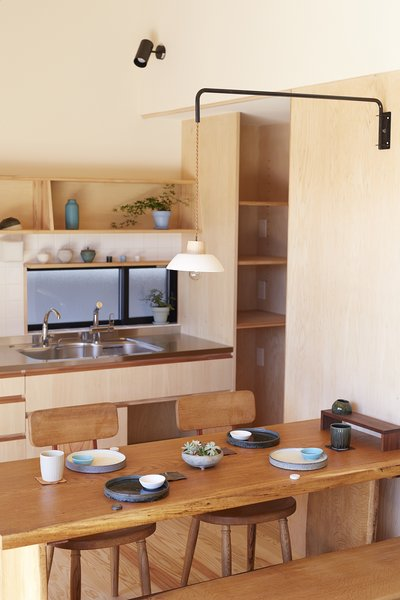 The homeowners have a taste for handmade items, including this dining room table and chairs, which they had custom made by a local woodworker. The facuet is from Kakudai and the pendant light is from iitaka kousaku.