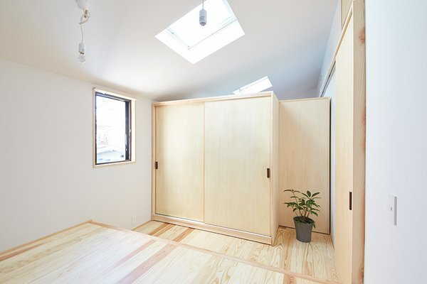 In addition to pull-out cabinets, the second-floor sleeping space can be reconfigured with movable partitions and wardrobes. Here, they divide the space into a two-bedroom arrangement. Photo 8 of Yanagisaki House modern home