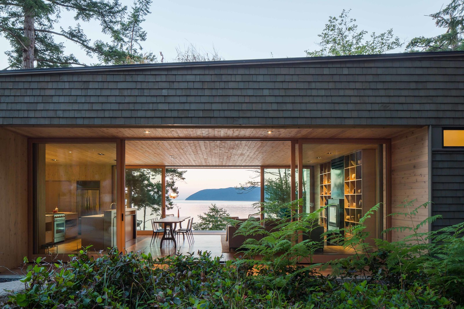 """""""The home is quite small, but designed in such a way that you don't feel it,"""" Herrin says. Lift-slide openings by Quantum Windows & Doors, which were fabricated fewer than 50 miles from the house, make the main living space seem larger. Tagged: Exterior, Shrubs, Wood Siding Material, Cabin Building Type, and House.  San Juan Islands Residence by Kelly Dawson"""