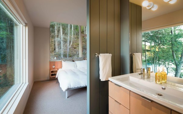 A Design Within Reach bed is steps away from a Second Floor sink by Duravit that's outfitted with an Essence Grohe faucet. Benjamin Moore's Templeton Gray is painted on the master bathroom's wood paneling.