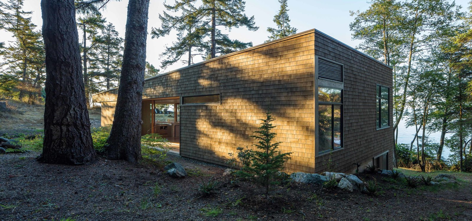"""The liberal use of wood roots the structure in the landscape and provides the owners with an experience strongly connected with location,"" Herrin says. The exterior's Western red cedar shingle siding has a semi-transparent stain, half Fieldstone and half Burnt Hickory from Cabot. Tagged: Exterior and Wood Siding Material. San Juan Islands Residence by Kelly Dawson"
