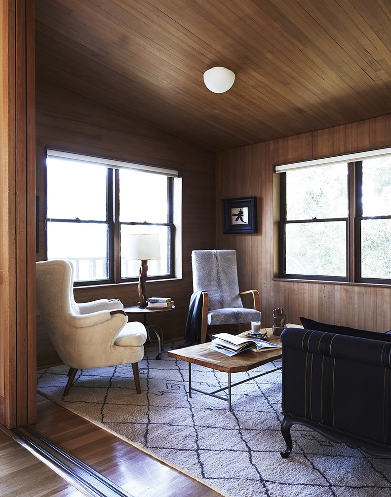 The cozy interior is wrapped in hemlock wood, which Esherick also used in the house he designed following this one in the Kent Woodlands area. A Thonet chair joins a Ben Soleimani rug for Restoration Hardware in the seating area.  Photo 6 of 10 in 10 Cozy Spaces and 15 Products to Help You Get Ready For Fall from Looking Good for Over 70 Years: This Cozy Joseph Esherick Home is Amazingly Well-Preserved
