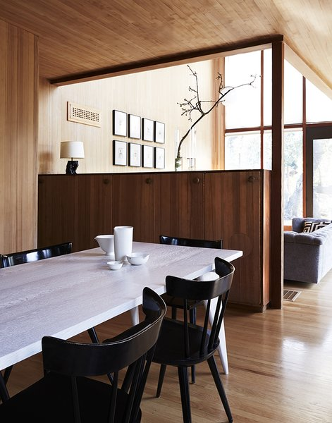 Original built-in cabinetry is retained throughout the house. Planner Group side chairs by Paul McCobb surround the dining table.