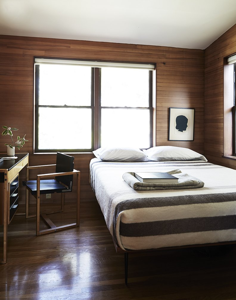 The rooms, featuring sloped ceilings, feel small and intimate. In the guest bedroom, there is a custom bed and a Swedish school desk found on eBay. Tagged: Bedroom, Bed, and Dark Hardwood Floor.  Bedrooms by Dwell from Looking Good for Over 70 Years: This Cozy Joseph Esherick Home is Amazingly Well-Preserved