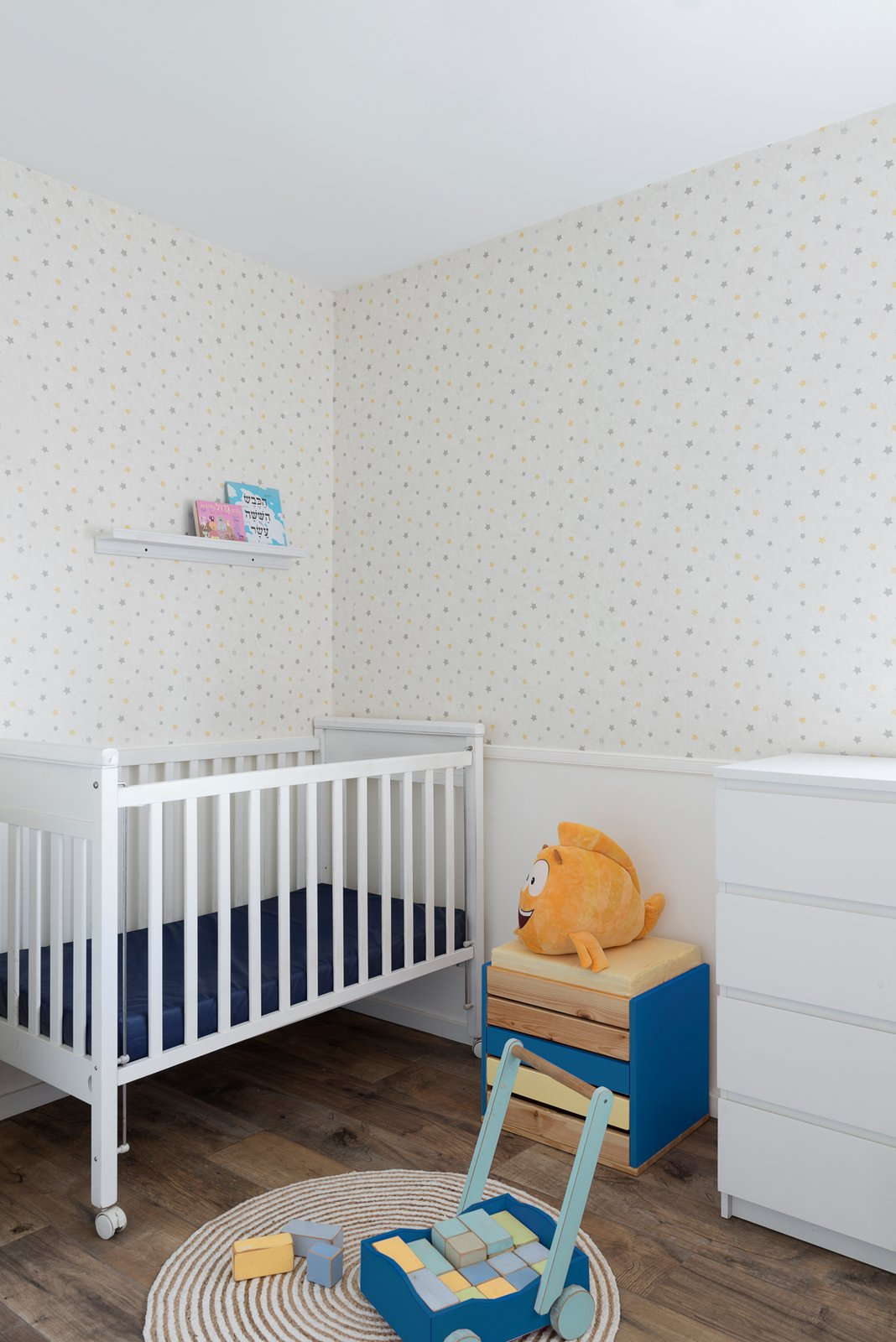 Although the color palette is minimal, the couple added bursts of blue and yellow throughout the home in the living room and even the new nursery.
