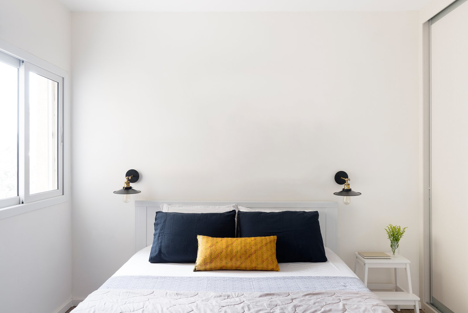 The bedroom is outfitted with a bed and side table from Ikea.  Bedroom by Mela Cortez from Expecting Couples Will Understand, Storage Is Everything at This Apartment