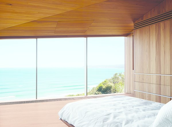 The couple, both surfers and beach lovers, wake up to stunning views of the azure-blue Southern Ocean in their otherwise monochromatic eucalyptus master bedroom. Wardle's firm designed the bed base, and the panel in the ceiling hides a television.