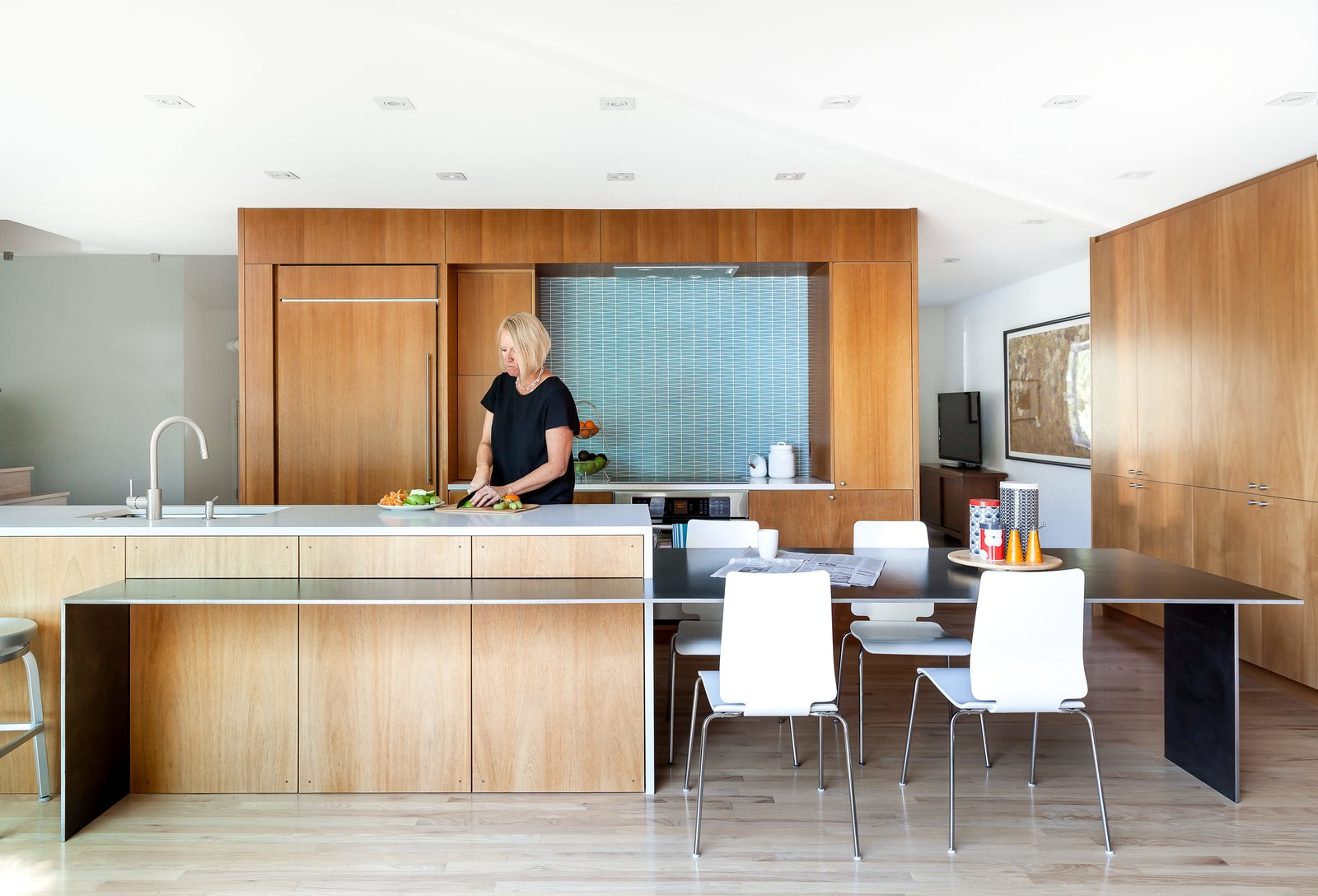 Hawkins removed walls and swapped outdated storage for floor-to-ceiling African mahogany cabinetry. Tagged: Kitchen, Glass Tile Backsplashe, and Wood Cabinet.  Photo 3 of 11 in A Completely Dysfunctional Nevada Kitchen Becomes Everyone's Favorite Spot for Parties