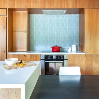 A Completely Dysfunctional Nevada Kitchen Becomes Everyone's Favorite Spot for Parties - Photo 8 of 11 - The stools are from Crate & Barrel. The Hobsons chose a geometric-patterned glass tile backsplash by Island Stone. Induction cooktop and oven are by Bosch.