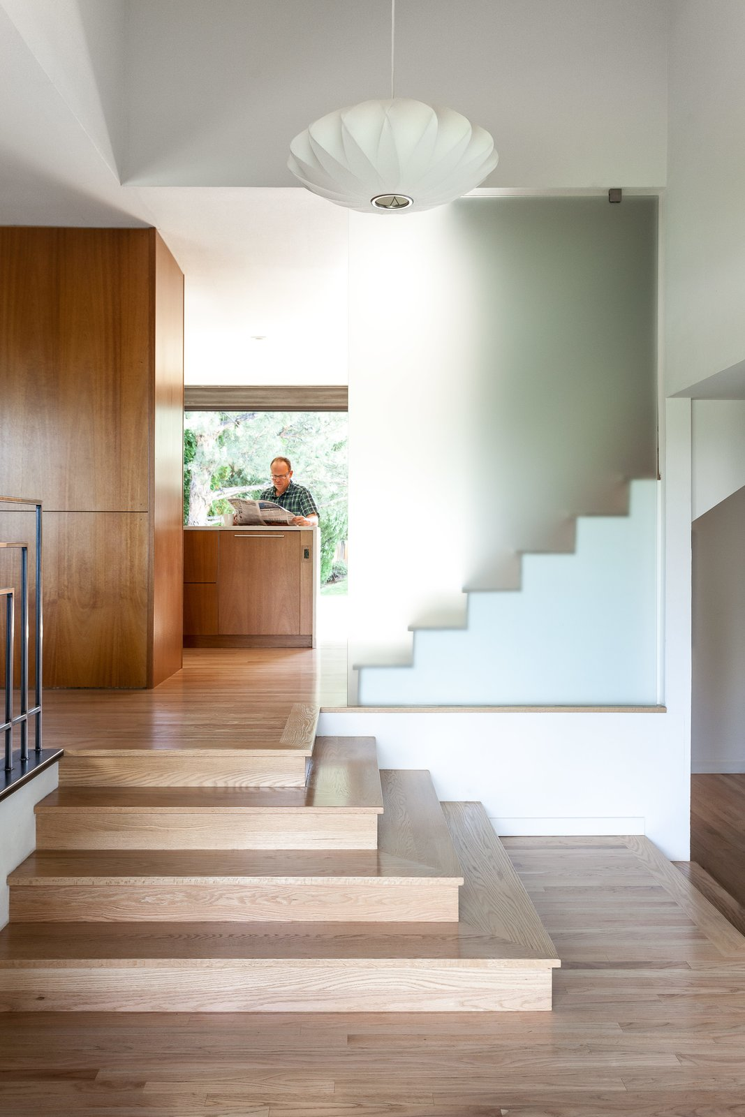 A George Nelson pendant hangs in the reconfigured entrance hall, whose stairs echo the concrete steps off the back deck.  190+ Best Modern Staircase Ideas by Dwell from A Completely Dysfunctional Nevada Kitchen Becomes Everyone's Favorite Spot for Parties