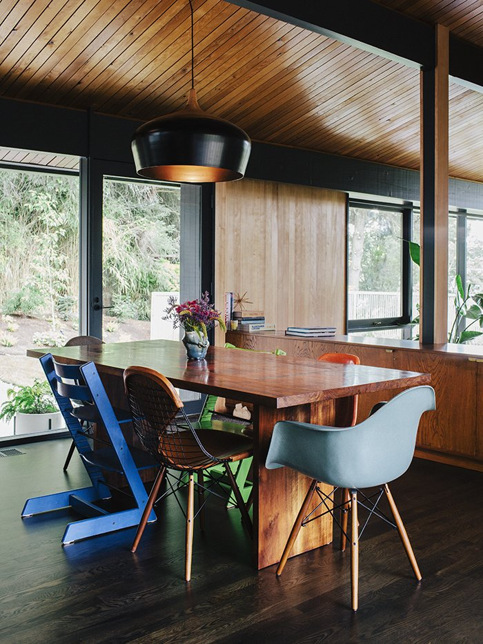An assortment of dining chairs, including vintage iterations on the Eames shell chair by Charles and Ray Eames and Stokke's Tripp Trapp chair, are clustered around a table lit by a pendant lamp by Coco Flip Design Studio. Tagged: Dining Room, Pendant Lighting, Table, and Chair. Midcentury Renovation in Portland Capitalizes on Nature with Seven Doors to the Outside - Photo 7 of 19