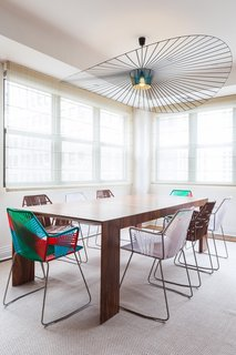 Pull Up a Chair in One of These 20 Modern Dining Rooms - Photo 18 of 20 - In the Tribeca penthouse of a young bachelor, Reddymade Design kept most of the space intact, focusing on adding bright and appealing furniture and materials. Tropicalia chairs from Moroso surround an El Dom table from Cassina. The pendant is from Petite Friture.