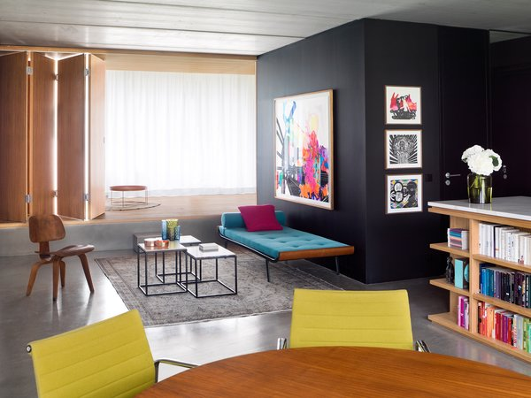 Architect Ester Bruzkus of Bruzkus Batek redesigned a compact apartment in Berlin to serve as her home. The previous layout had two bedrooms and one bathroom, but Bruzkus created an open-plan arrangement with only one bedroom to free up space. A folding wall can be pulled out for privacy. Custom furniture joins pieces by Charles and Ray Eames for Herman Miller and Gervasoni. The bathroom is enclosed within the black cube, which can be entered from either the bedroom side or the living room side. The paintings are by Berlin-based artist Niki Elbe.