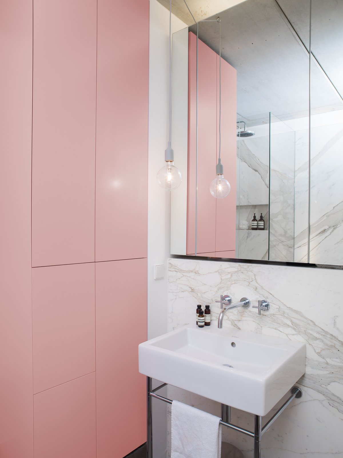 Statuario marble appears again in the bathroom, where it contrasts pink cabinets that create ample room for storage. Tagged: Bath Room, Stone Slab Wall, Pendant Lighting, and Pedestal Sink. Best Photos