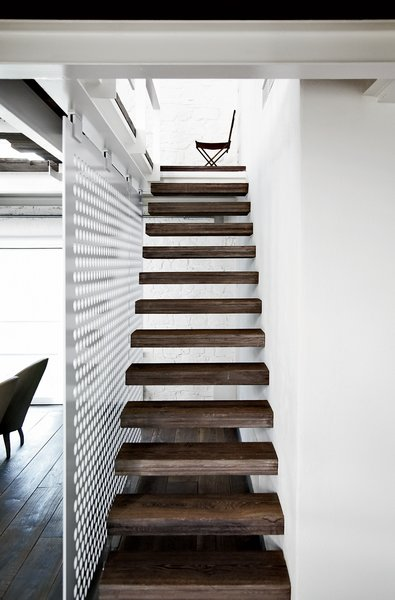 The upper level of the 5,300-square-foot space is accessed via a slender stair with reclaimed-wood treads.