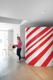 This Factory Switches Out Cattle-Fodder for Furniture - Photo 2 of 9 - Daughter Oona stands near the candy-striped wardrobe in the entryway.