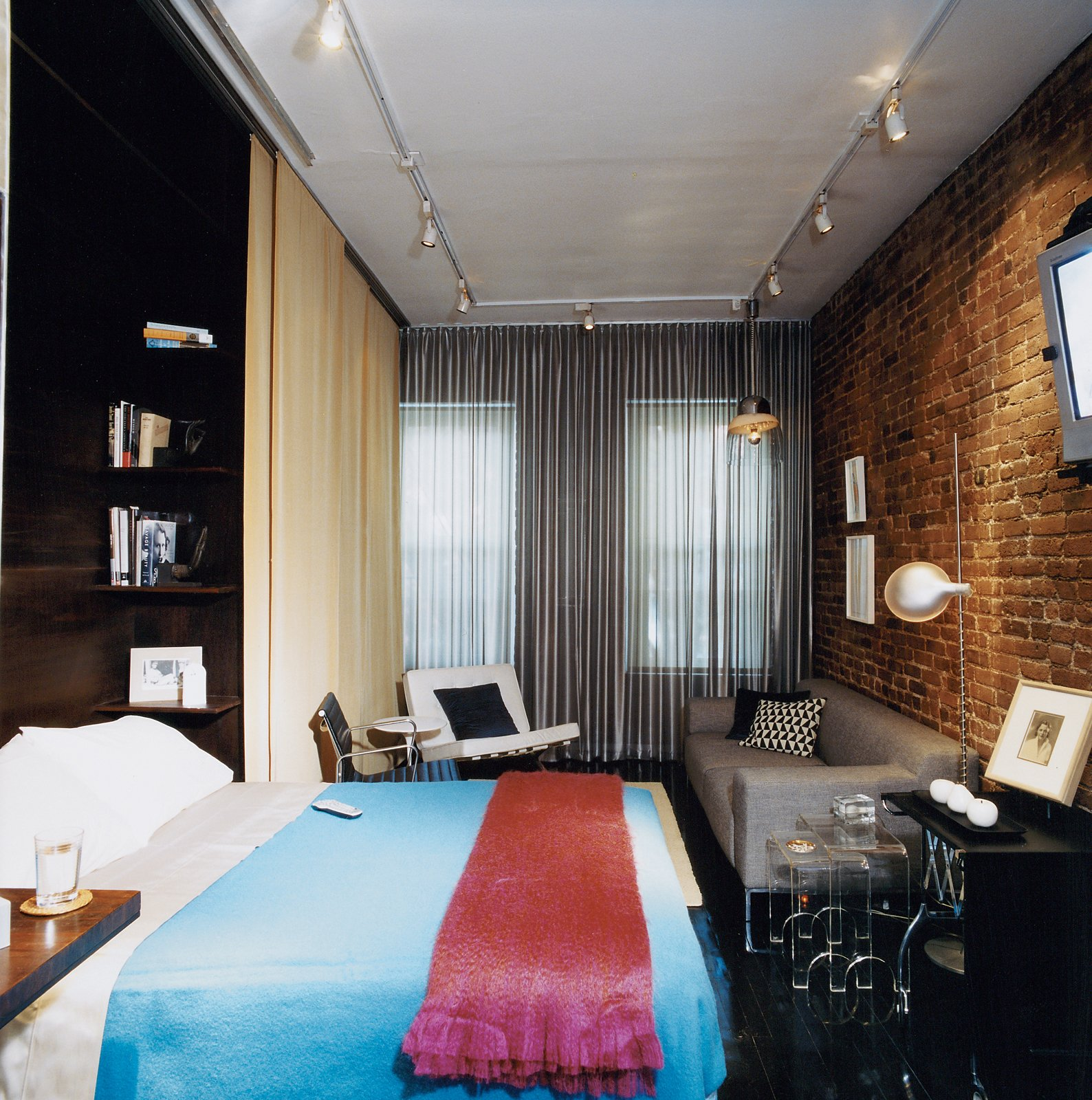 """""""I think of the bed as intimate space,"""" Hughston says, """"and putting the bed away—having it out of sight when not in use—is satisfying."""" The custom-designed Murphy bed, concealed by day behind the gold curtain is well built; it's ergonomically easy to lower and has a firm sleeping surface. Tagged: Bedroom, Bed, Shelves, Track Lighting, Dark Hardwood Floor, Pendant Lighting, Night Stands, and Chair.  Tiny Apartments in New York City by Allie Weiss from A 400-sq-ft New York Apartment Gets a Second Chance"""