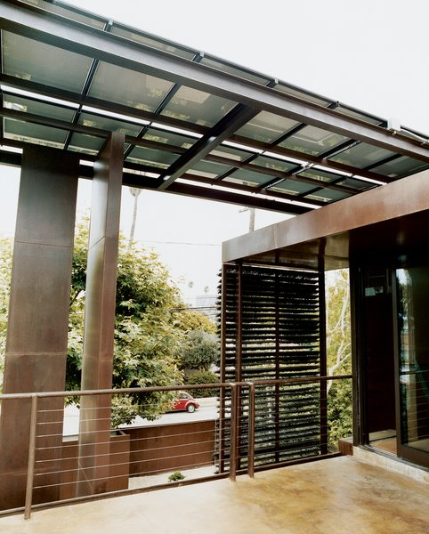 A steel-beam canopy with solar panels shades the house and provides electricity.