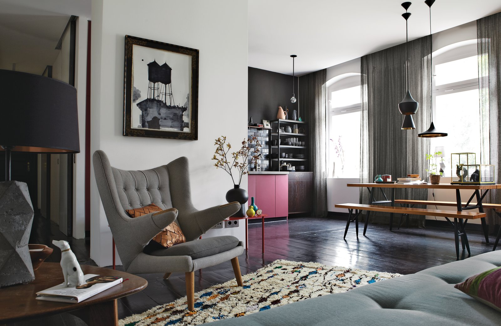 The old wood floors throughout the open-plan space are painted a dark eggplant. The vintage PP19 armchair is by Hans J. Wegner for PP Møbler. The painting above it is by Ruben Toledo, a friend of Peter Fehrentz, the resident. A trio of Tom Dixon lights hangs over the Pirkka dining table, with bench seating by Ilmari Tapiovaara for Artek. The Berber rug is from Morocco, purchased from the Paris shop Caravane. Tagged: Living Room, Pendant Lighting, Chair, Sofa, Coffee Tables, and Dark Hardwood Floor.  127+ Inspiring Interior Ideas by Dwell from Inside Peter Fehrentz's Renovated Flat in Berlin