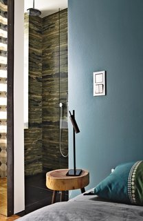 A sliding door divides the verde bamboo granite bathroom from the bedroom.