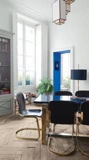 The dining room features 1970s leather-and-brass dining chairs and a table concocted from a brass-and-silver base and a custom lacquered top. The cheerful blue paint enlivening the doorway is from Emery & Cie.