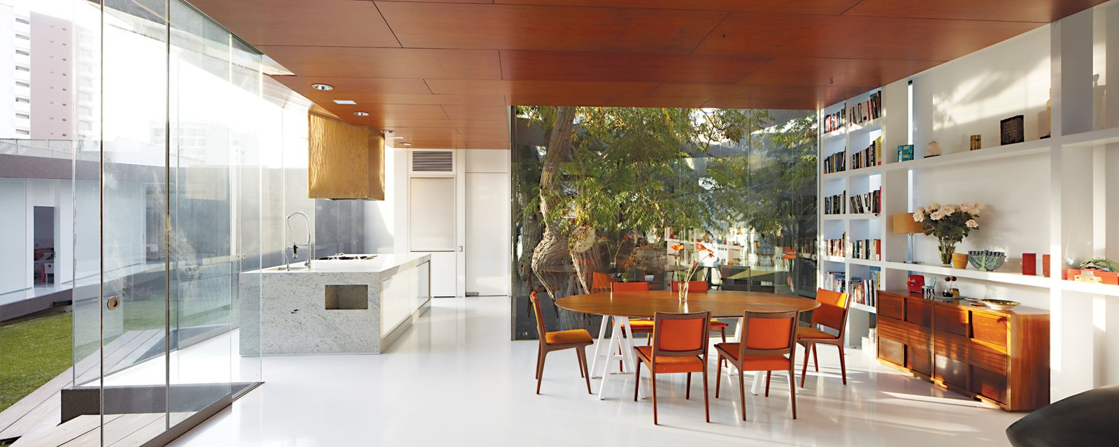 The dining area holds an adjunct kitchen designed for Lisette, a chef; the table base was repurposed from one from her former restaurant.  Photo 3 of 13 in A Modern Concrete Home in Peru