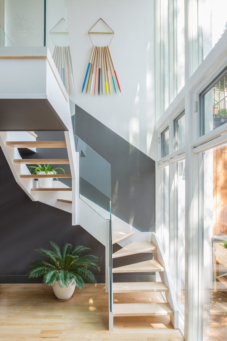 The back staircase abuts a glass facade overlooking the backyard and allowing plenty of light into the kitchen area above. The art hanging on the wall is by artist Julie Thevenot.