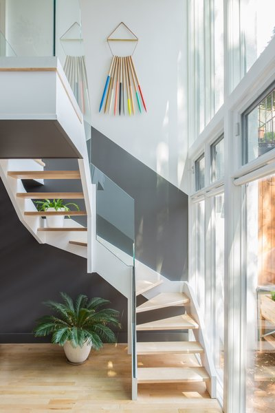 The back staircase abuts a glass facade overlooking the backyard and allowing plenty of light into the kitchen area above. The art hanging on the wall is by artist Julie Thevenot. Photo 5 of Color Splash modern home