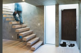 Open-Plan Concrete Home in Japan - Photo 5 of 7 - Tsutsui continued the Oregon pine from the floor to the steel-reinforced cantilevered staircase, which appears to float above the floor.