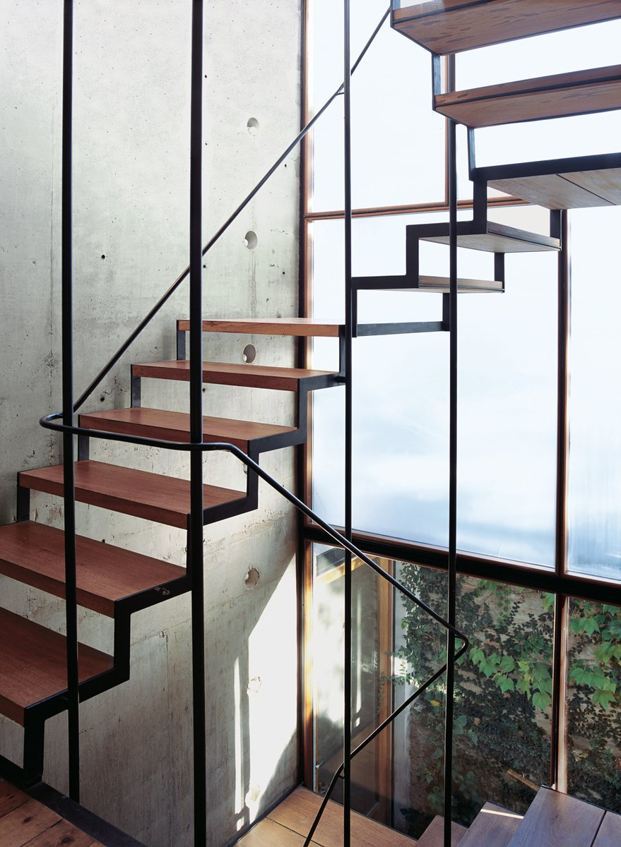 Argentinean materials, a roiling economy, and a pinch of personal tumult served as the recipe for furniture designer Alejandro Sticotti's Buenos Aires oasis. The wood-and-steel open staircase wends its way up three stories, supported by a concrete structural wall embedded with PVC tubes and bare lightbulbs. Photo by: Cristóbal Palma  190+ Best Modern Staircase Ideas by Dwell from Staircases We Love