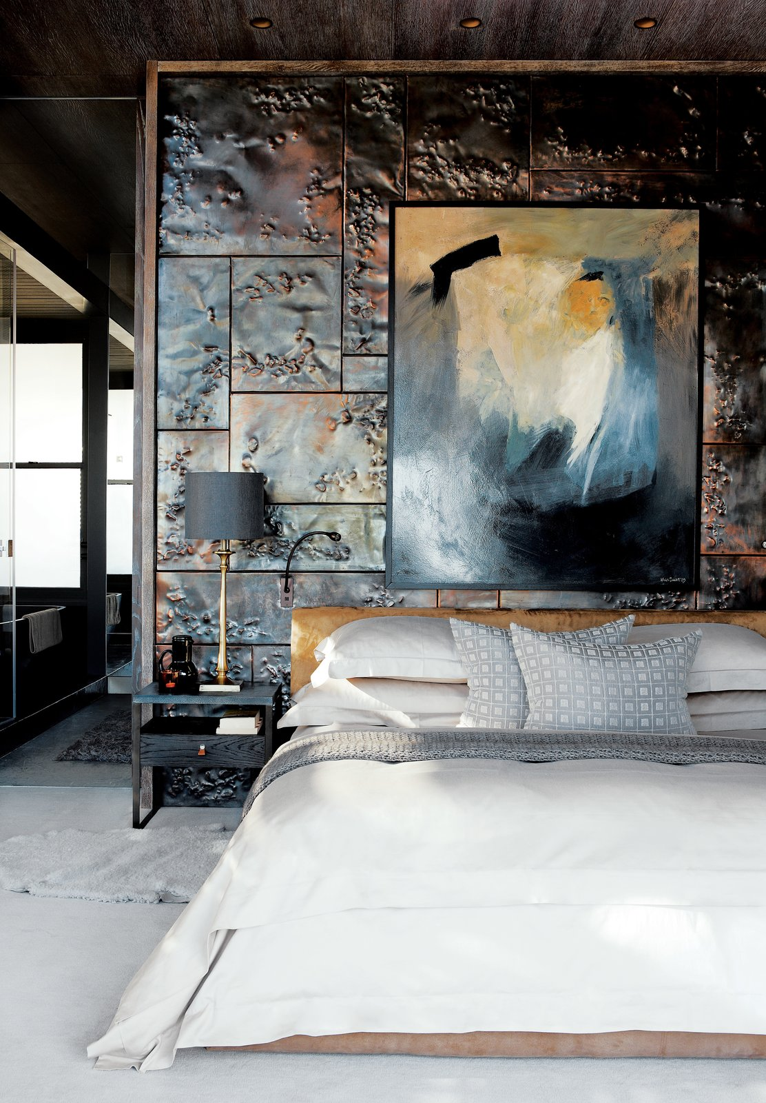 Custom hammered-copper tiles add texture and reflect light in the master bedroom. The bed, steel-and-walnut side tables, and brass lamps are all custom-made by Cécile & Boyd's.  Bedrooms by Dwell from A Sophisticated Penthouse in Cape Town