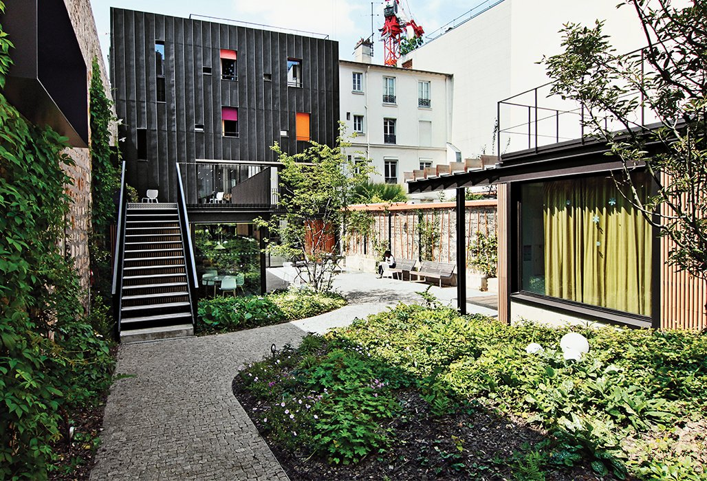 Architect Damien Brambilla turned a run-down Paris apartment building into an open, bright adolescent group home with a landscaped garden. Tagged: Outdoor, Back Yard, Hardscapes, Garden, Walkways, and Gardens.  Photo 9 of 10 in 10 Modern Renovations to Unique Homes in France from How California Style Influenced a Group Home in Paris