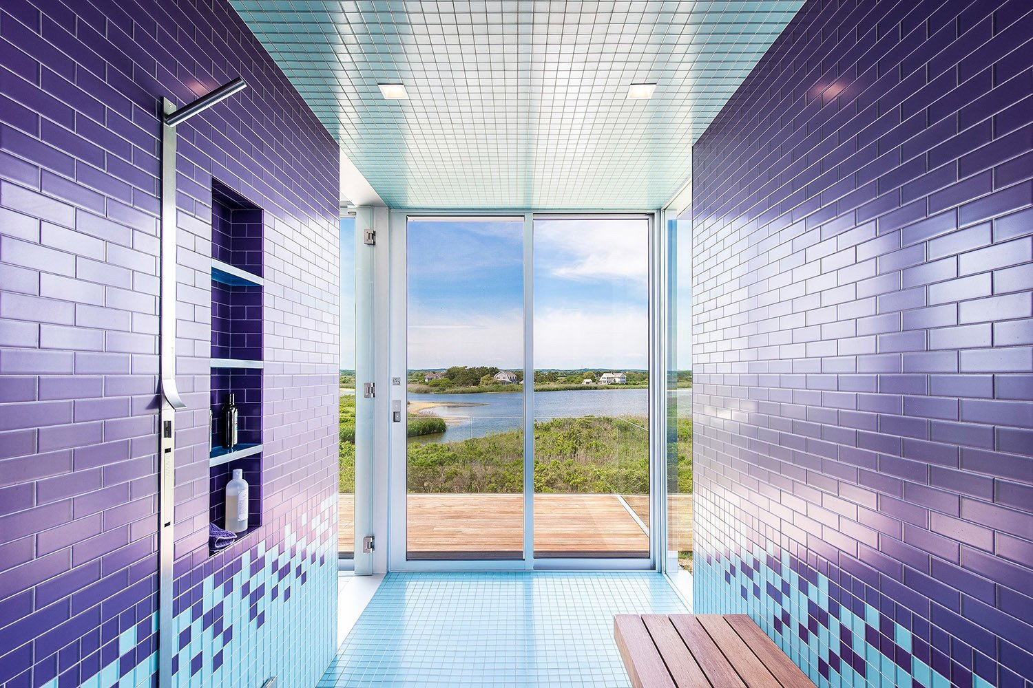 Consider this lively bathroom that sits within a recently completed waterfront home in Bridgehampton, New York. Situated on two-and-a-half acres of land with 360-degree views of the nearby bay and ocean, it's covered with brightly colored floor-to-ceiling tiles that reflect the shades of the neighboring water. One step through the sliding glass doors and you'll find yourself on an open terrace.