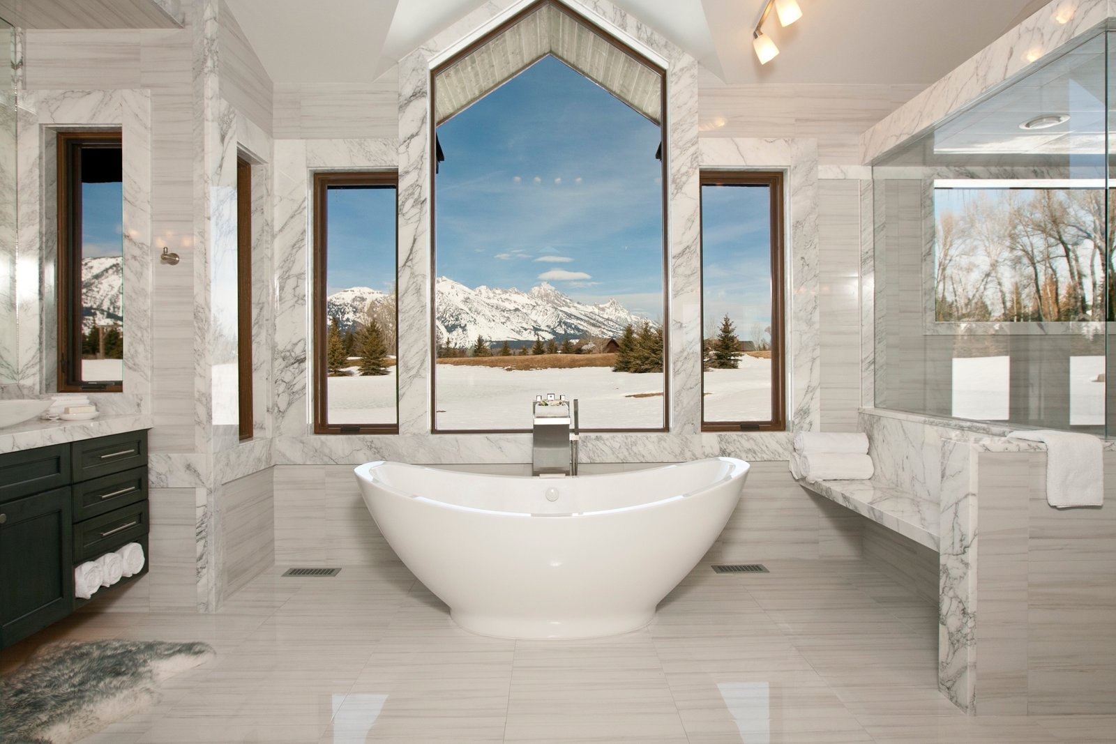 Making our way to Jackson Hole, Wyoming, this master suite bathroom is nestled within a mountain retreat that sits on five acres of private land. Slabs of Carrera marble line the space while the central window overlooks the Grand Teton national park. Placed at the edge of the bathroom is a 50-square-foot shower with steam capabilities.  Photo 17 of 22 in Bath & Spa Intrigue from One of These Ultra-Modern Bathrooms Could Be the Escape of Your Dreams