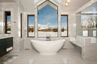Bath & Spa Intrigue - Photo 16 of 21 - Making our way to Jackson Hole, Wyoming, this master suite bathroom is nestled within a mountain retreat that sits on five acres of private land. Slabs of Carrera marble line the space while the central window overlooks the Grand Teton national park. Placed at the edge of the bathroom is a 50-square-foot shower with steam capabilities.