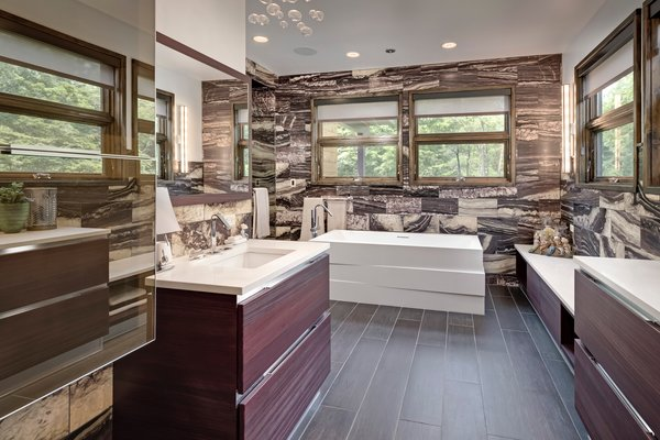 Our last stop is at a private retreat in Illinois that features four bedrooms, four-and-a-half baths, and a four-car heated garage. The distinctly dark style of marble lining the walls of the bathroom helps forge a space that reflects its natural surroundings.