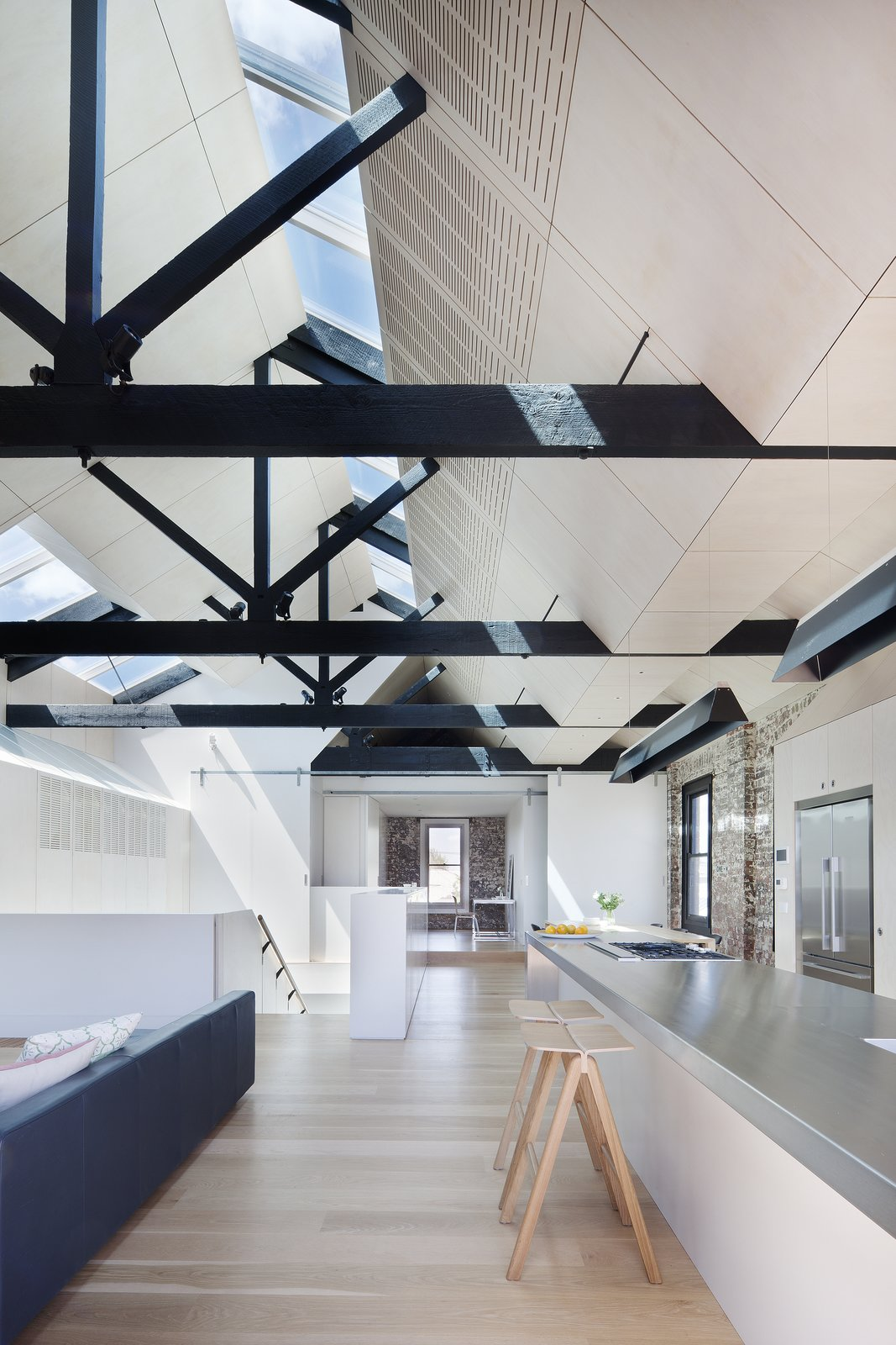 """The fact that the external walls were built to the site's boundary led to the solution of skylights as the one of the few means of introducing north light and good cross ventilation into the building,"" Simpson continues. The hanging lights are from Artemide while the hotplates and cooktops are from Barazza."