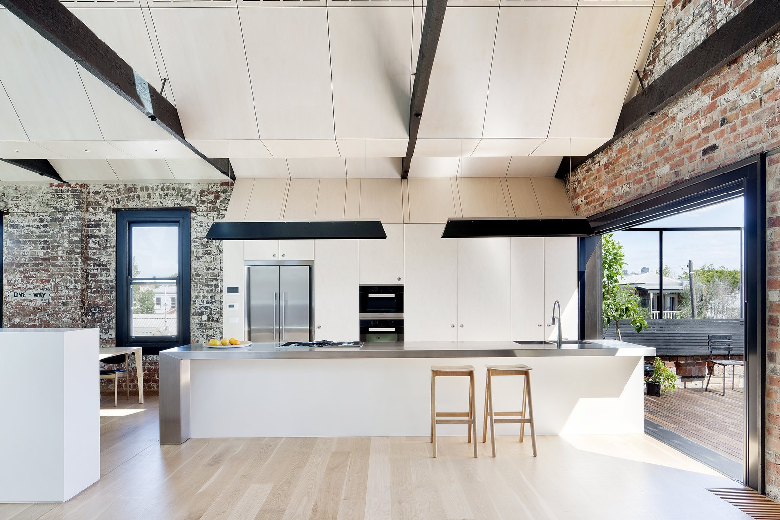 The kitchen, which also features an oven by Miele, is separated from an outdoor deck by an A14 sliding door by Centor.  Water Factory by Kelly Dawson