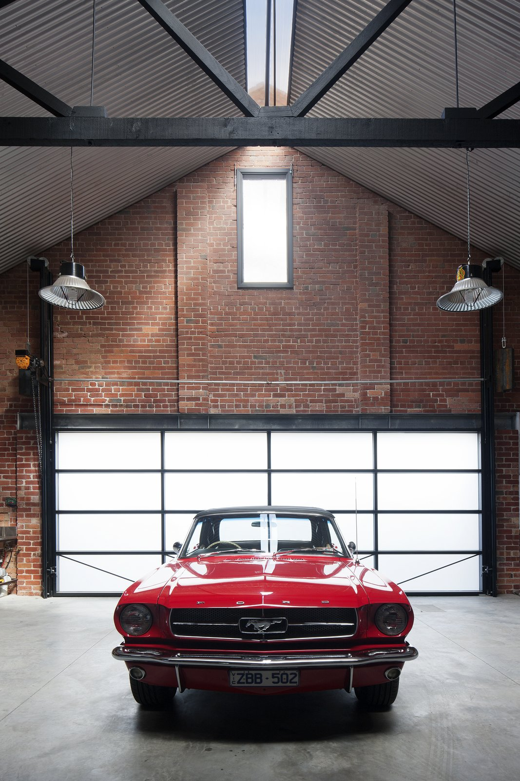 "The owners are car collectors, especially of ""vintage American Mustangs,"" Simpson says, so a nearly 23-foot-wide garage door opening was created at the rear of the building to access a space made for six prized rides. Tagged: Garage.  Water Factory by Kelly Dawson"