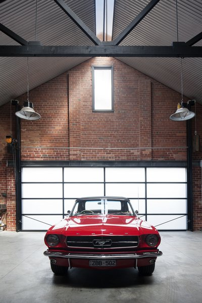"Modern home with garage. The owners are car collectors, especially of ""vintage American Mustangs,"" Simpson says, so a nearly 23-foot-wide garage door opening was created at the rear of the building to access a space made for six prized rides. Photo 9 of Water Factory"
