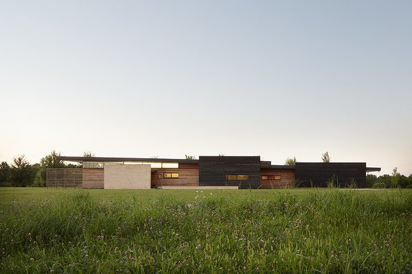 """Cedar rainscreen in a range of widths and color stains makes up the facade. The low-slung exterior was designed to respond to the surrounding topography. """"The design of the house provides a subtle, and at times, dramatic response to the open Midwestern terrain and offers a contemporary interpretation of 'prairie style' architecture,"""" El Dorado Inc principal Josh Shelton says."""