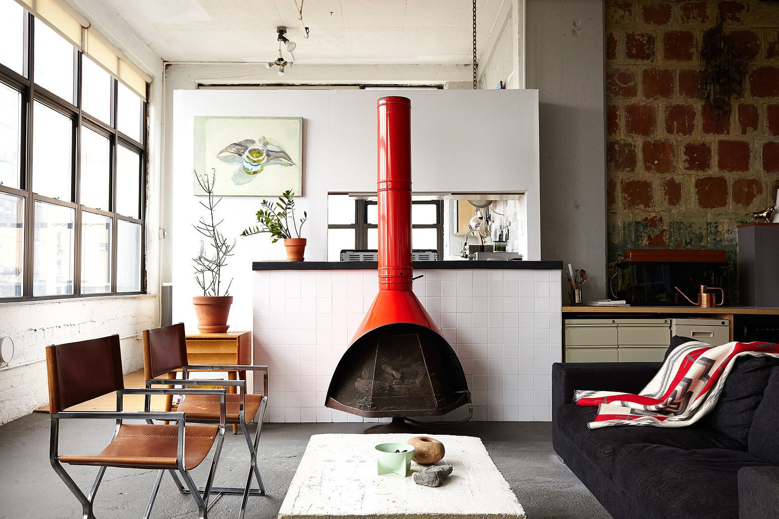 """I'm not trying to hide anything. I wanted to stay true to the industrial look,"" explains Owen Wright, the owner of this Brooklyn loft. Owen works with his building's landlord and consequently has accrued countless pieces of furniture from both former tenants and Craigslist—including this 1960's fireplace and pair of steel frame chairs Owen had reupholstered. A BoConcept sofa and coffee table Owen constructed himself complete the living room. 97+ Modern Fireplace Ideas by Dwell"