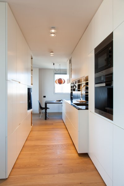 Two custom built-in structures form a corridor-like workspace in the kitchen. The appliances are by Miele, and the steel-and-black glass sink is from Franke.