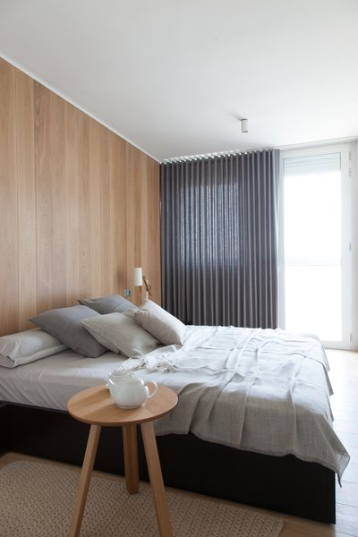 A black-laquered bed frame and side tables by Besform furnish the master bedroom, where the wood-clad accent wall both continues the oak motif and acts as a minimal headboard accent. The bed linens are by Kokoklim and the linen curtains are by Acor.